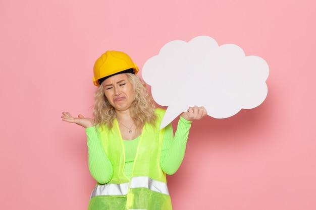 Junge weibliche baumeisterin der vorderansicht im gelben helm des grünen bauanzugs, der großes weißes zeichen hält, das auf dem rosa raumjobarchitekturbaujob lächelt