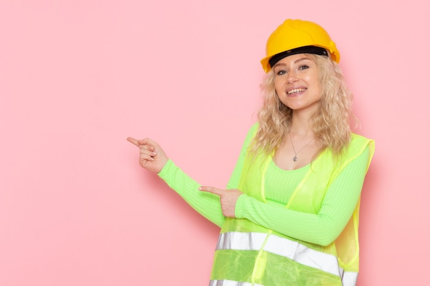 Junge weibliche baumeisterin der vorderansicht im gelben helm des grünen bauanzugs, der lächelt und auf dem konstruktionsfoto der rosa raumjobarchitektur hervorhebt