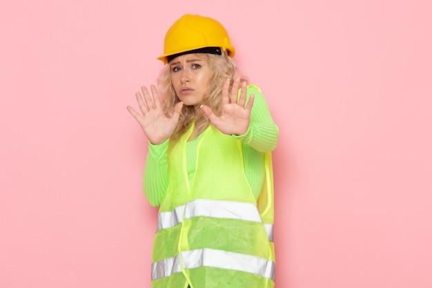Junge weibliche baumeisterin der vorderansicht im gelben helm des grünen bauanzugs, der mit vorsicht auf dem rosa raumjobarchitektur-konstruktionsfoto aufwirft