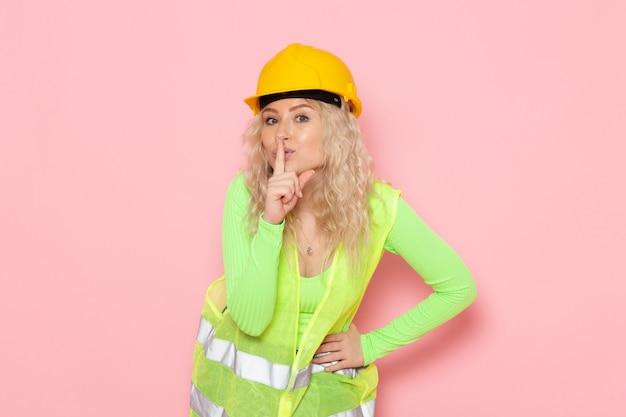 Junge weibliche baumeisterin der vorderansicht im gelben helm des grünen bauanzugs, der stillezeichen auf dem rosa raumjobarchitektur-konstruktionsfoto zeigt