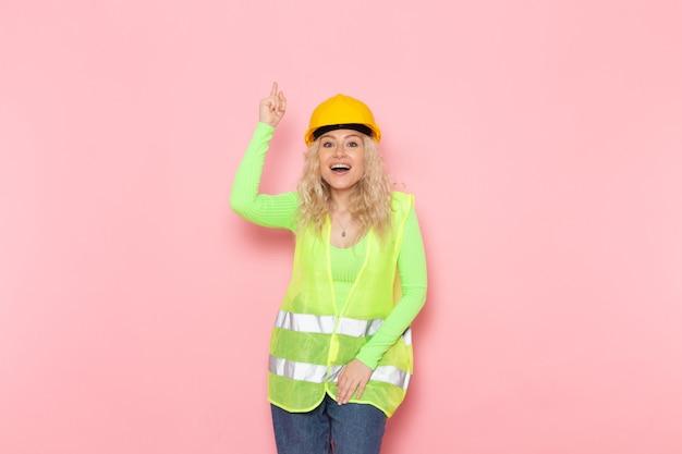 Junge weibliche baumeisterin der vorderansicht im gelben helm des grünen bauanzugs lächelnd mit erfreutem ausdruck auf dem konstruktionsfoto der rosa raumjobarchitektur