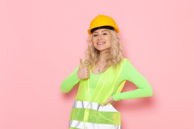 Junge weibliche baumeisterin der vorderansicht im gelben helm des grünen bauanzugs lächelnd und posierend auf dem konstruktionsfoto der rosa raumjobarchitektur