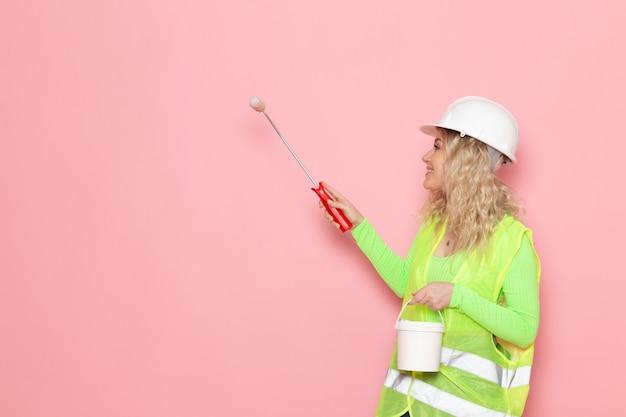 Junge weibliche baumeisterin der vorderansicht im grünen bauanzug-helm, der wände auf den rosa raumarchitektur-bauarbeiten malt