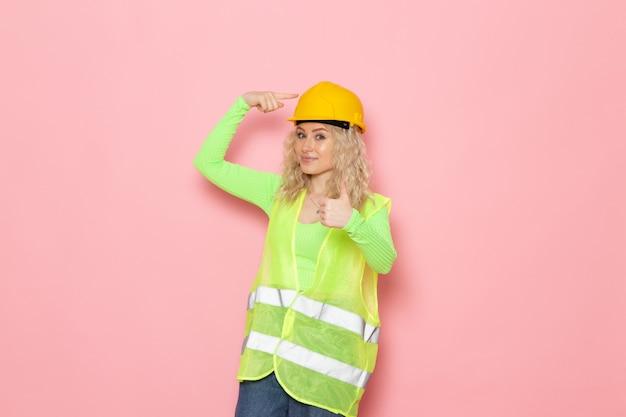 Junge weibliche baumeisterin der vorderansicht im grünen bauanzughelm, der gerade mit lächeln auf der rosa raumarchitektur-bauarbeit aufwirft