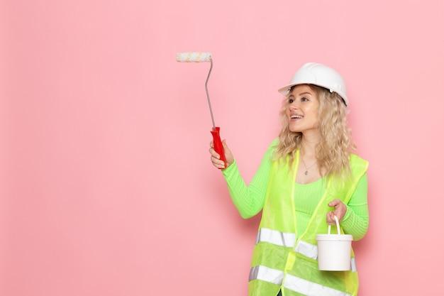 Junge weibliche baumeisterin der vorderansicht im grünen bauanzughelm, der weiße farbe mit lächelnmalerei auf dem rosa raum hält