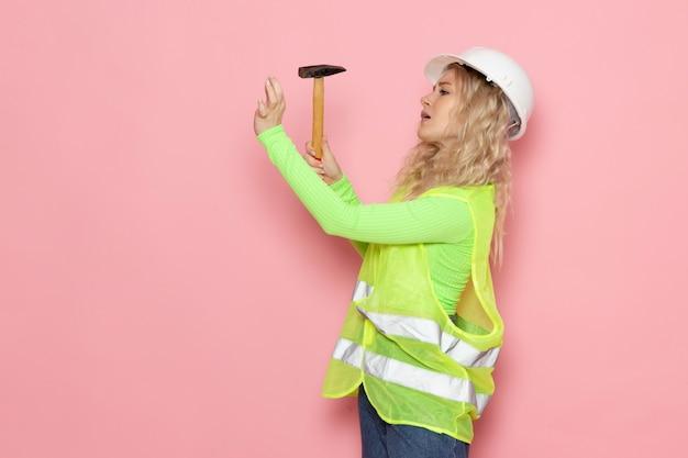 Junge weibliche baumeisterin der vorderansicht im weißen helm des grünen bauanzugs unter verwendung eines hammers auf dem rosa raumjobarchitekturbaujob