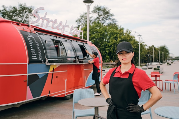 Junge weibliche besitzerin von food truck, die vor der kamera steht