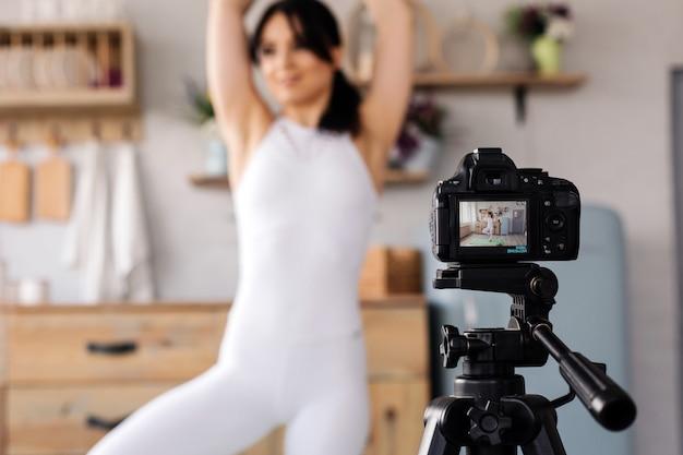 Junge weibliche bloggeraufnahme trägt video zu hause zur schau