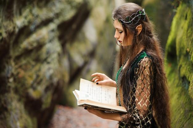 Junge weibliche elfe, die in den wald hält ein altes buch wandert