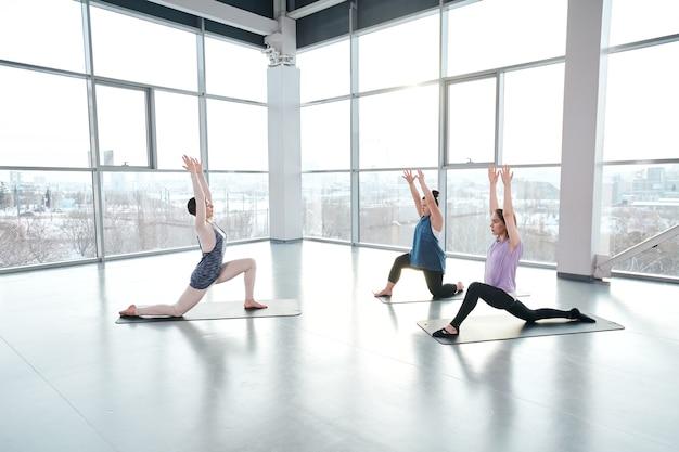 Junge weibliche fitnesstrainerin und zwei aktive frauen in sportbekleidung, die mit erhobenen händen auf einem knie stehen und zusammengesetzt sind