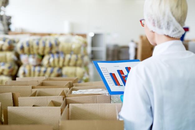 Junge weibliche fokussierte arbeiterin in sterilen tüchern überprüft karten aus ihrem ordner, während sie in der nähe der kisten im fabriklager steht und sie zählt.