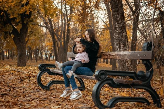 Junge weibliche frauenbabysitter und kleinkindbaby gehen im herbstpark glückliche familienmutter und -kleinkind