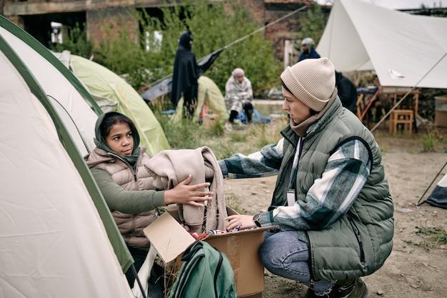 Junge weibliche freiwillige, die kleidung an kind weitergeben