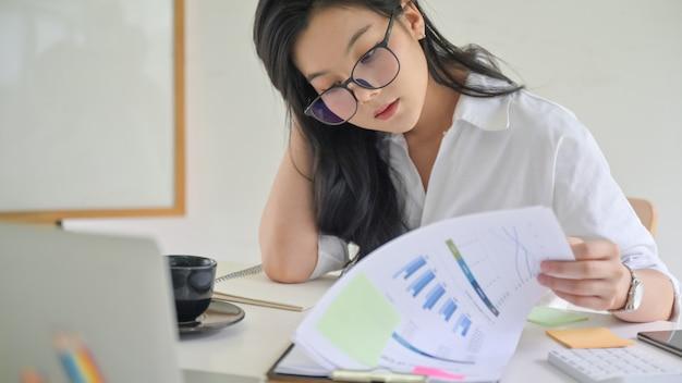 Junge weibliche führungskraft überprüft die leistung des unternehmens.