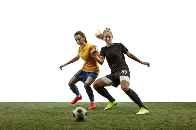 Junge weibliche fußball- oder fußballspieler mit langen haaren im sportbekleidungs- und stiefeltraining