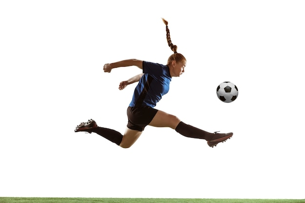 Junge weibliche fußball- oder fußballspielerin mit langen haaren, die den ball für das ziel im flug treten und hoch auf weißem studiohintergrund springen. konzept eines gesunden lebensstils, profisport, bewegung, bewegung.