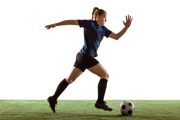 Junge weibliche fußball- oder fußballspielerin mit langen haaren in sportbekleidung, die ball für das ziel tritt, training auf weißem studiohintergrund. konzept eines gesunden lebensstils, profisport, bewegung, bewegung.