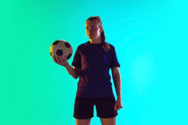 Junge weibliche fußball- oder fußballspielerin mit langen haaren in sportbekleidung, die ball hält und selbstbewusst auf farbverlaufshintergrund posiert, neon. konzept eines gesunden lebensstils, profisport, bewegung, bewegung.