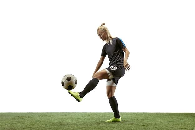 Junge weibliche fußball- oder fußballspielerin mit langen haaren in sportbekleidung und stiefeln, die den ball für das ziel im sprung auf weißem hintergrund treten. konzept eines gesunden lebensstils, profisport, bewegung, bewegung.