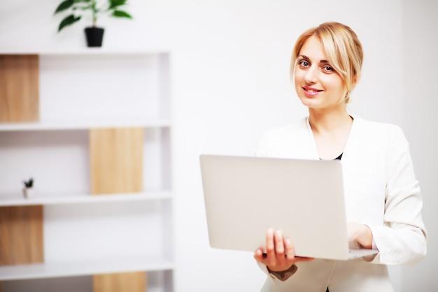 Junge weibliche geschäftsfrau, die in ihrem büro auf laptop arbeitet