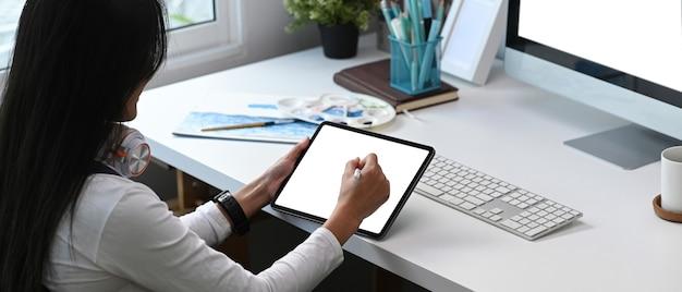 Junge weibliche grafikdesigner-handzeichnung auf computertablett an ihrem kreativen arbeitsbereich