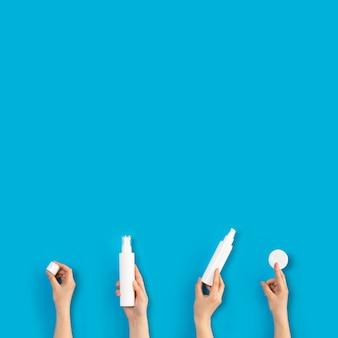 Junge weibliche hände, die plastikrohr auf blauem hintergrund halten