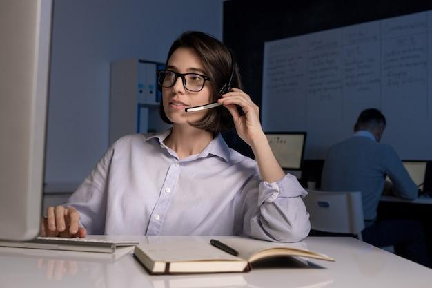 Junge weibliche hotline-betreiberin mit headset, die mit kunden online vor computerbildschirm spricht