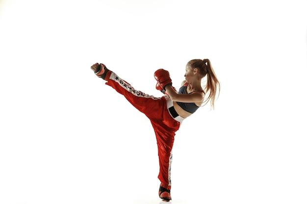 Junge weibliche kickboxkämpferausbildung lokalisiert auf weißer wand. kaukasisches blondes mädchen in der roten sportbekleidung, die in den kampfkünsten praktiziert. konzept von sport, gesundem lebensstil, bewegung, aktion, jugend. Kostenlose Fotos