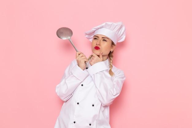 Junge weibliche köchin der vorderansicht im weißen anzug, der silbernen löffel auf dem arbeitsfoto der rosa raumkochküche hält