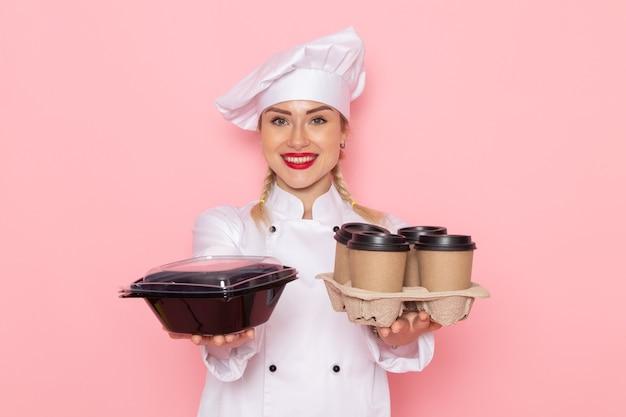 Junge weibliche köchin der vorderansicht im weißen kochanzug, der plastikkaffeetassen und lebensmittelverpackung auf dem rosa raumkochfoto hält