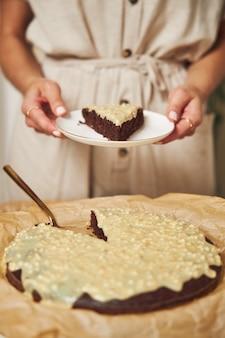 Junge weibliche köchin, die einen köstlichen schokoladenkuchen mit sahne auf einem weißen tisch macht