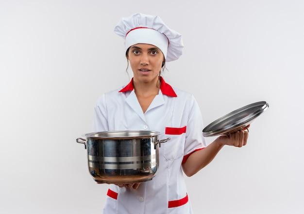 Junge weibliche köchin, die kochuniform trägt, die topf und deckel auf isolierter weißer wand mit kopienraum hält