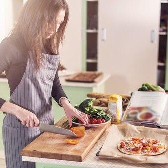 Junge weibliche köchin hackt zutaten für pizza auf schneidebrett nach dem rezept geschrieben in einem buch, das in der küche steht