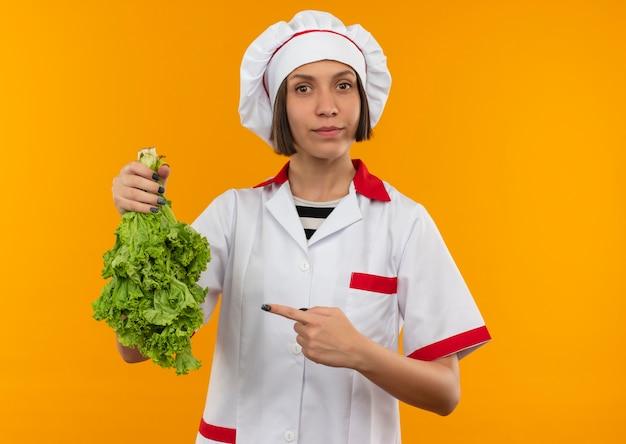 Junge weibliche köchin in der kochuniform, die auf salat hält und zeigt und kamera lokalisiert auf orange hintergrund betrachtet