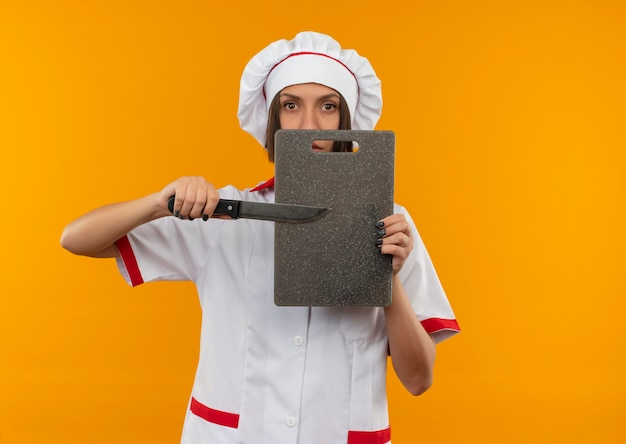 Junge weibliche köchin in der kochuniform, die mit messer auf schneidebrett zeigt und kamera lokalisiert auf orange hintergrund mit kopienraum betrachtet