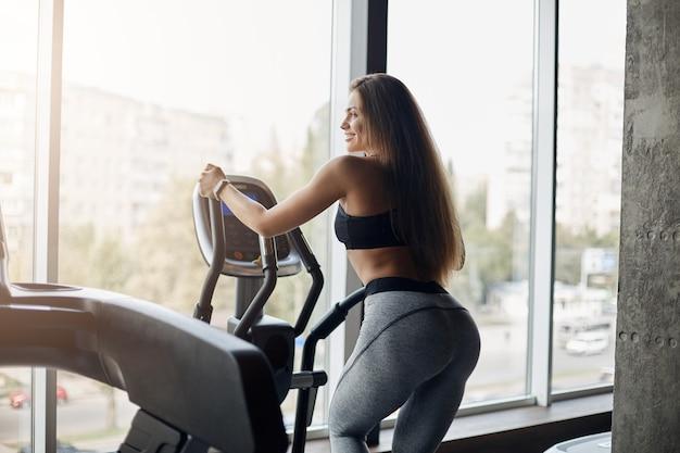 Junge weibliche körperfitness-trainerin, die elliptischen cross-trainer verwendet, um sich vor einem langen harten arbeitstag am frühen morgen aufzuwärmen. gesäß trainieren.