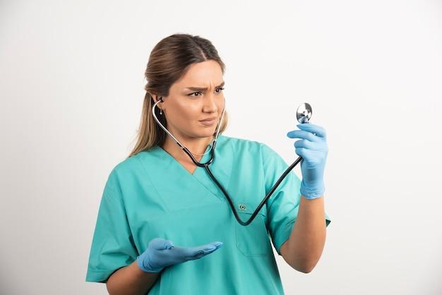 Junge weibliche krankenschwester, die mit stethoskop aufwirft.