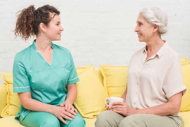 Junge weibliche krankenschwester, welche die ältere frau hält tasse kaffee betrachtet