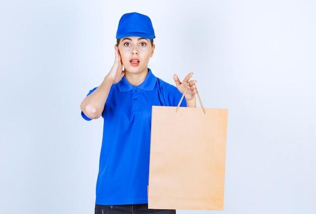 Junge weibliche kurier, die papierhandwerkstasche tragen und auf weißem hintergrund stehen.