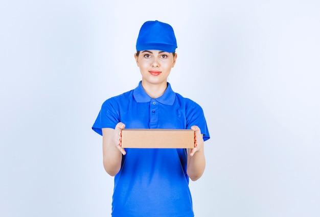 Junge weibliche kurier in blauer uniform verschenken karton auf weißem hintergrund.