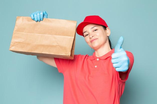 Junge weibliche kurier in rosa t-shirt rote kappe blaue handschuhe halten box an der blauen wand
