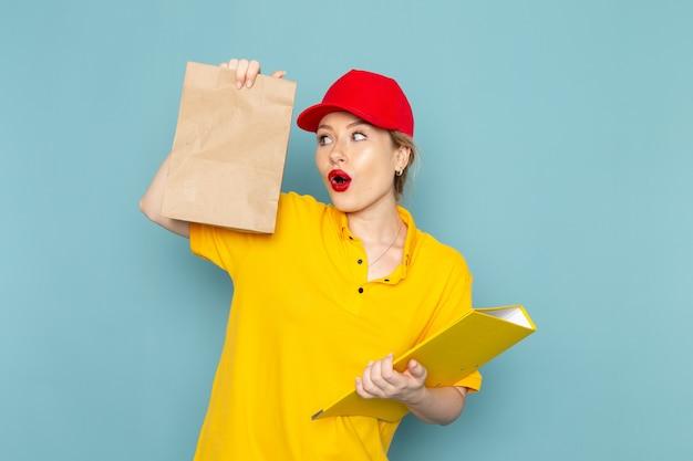 Junge weibliche kurierin der vorderansicht im roten umhang des gelben hemdes, das paket und gelbe datei auf dem blauen raumarbeiter hält