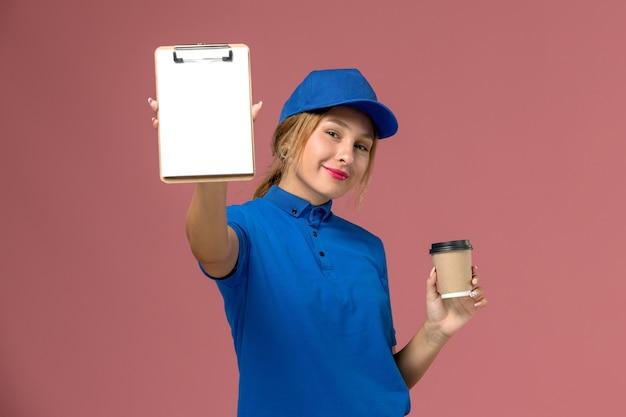 Junge weibliche kurierin der vorderansicht in der blauen uniform, die das halten der tasse kaffee und des notizblocks lächelnd, dienstuniform-zustellungsfrauenjobarbeiterfoto aufwirft