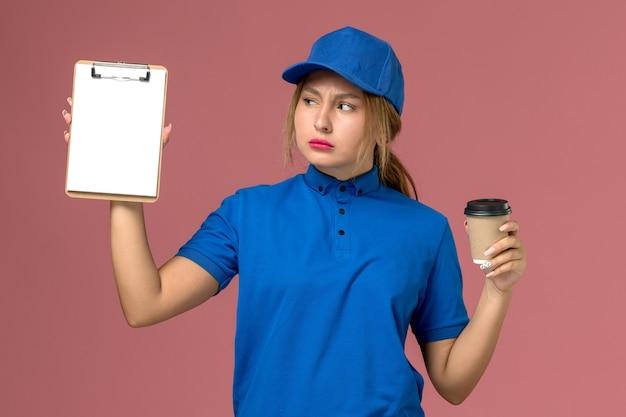 Junge weibliche kurierin der vorderansicht in der blauen uniform, die die tasse kaffee und den notizblock aufwirft, dienstuniform-zustellfrau-jobarbeiter
