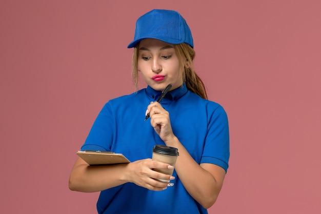 Junge weibliche kurierin der vorderansicht in der blauen uniform, die die tasse kaffee und den notizblock denkend aufstellt, dienstuniformlieferungsfrauenjob
