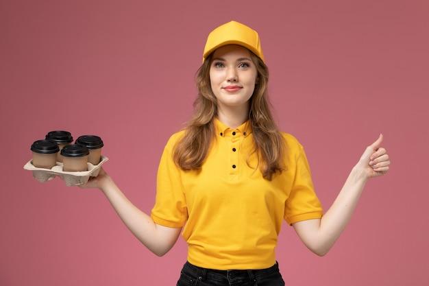 Junge weibliche kurierin der vorderansicht in der gelben uniform, die kaffeetassen hält und auf dem rosa hintergrundschreibtischjobuniformlieferdienstarbeiter lächelt