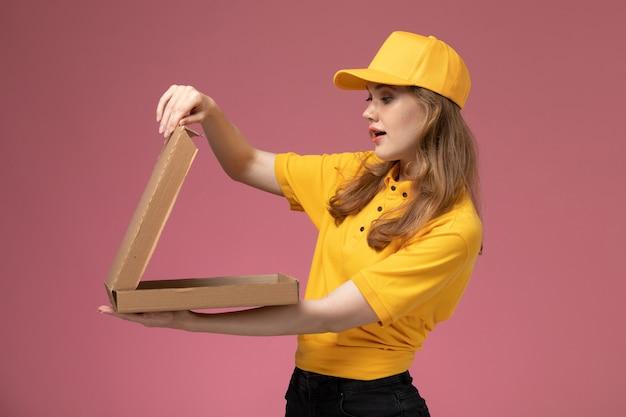 Junge weibliche kurierin der vorderansicht in der gelben uniform, die lieferung-nahrungsmittelbox hält, die es auf dem rosa schreibtischjobuniform-lieferservice-arbeiter öffnet