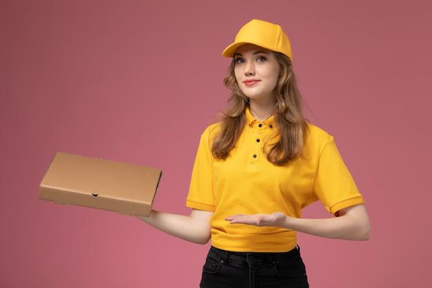Junge weibliche kurierin der vorderansicht in der gelben uniform, die lieferung-nahrungsmittelbox lächelnd auf rosa schreibtischjobuniform-lieferservice-arbeiter hält
