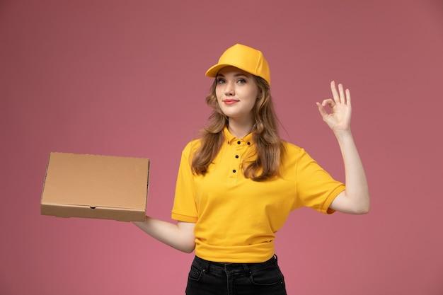 Junge weibliche kurierin der vorderansicht in der gelben uniform, die lieferung-nahrungsmittelbox mit lächeln auf rosa schreibtischjobuniform-lieferservice-arbeiter hält