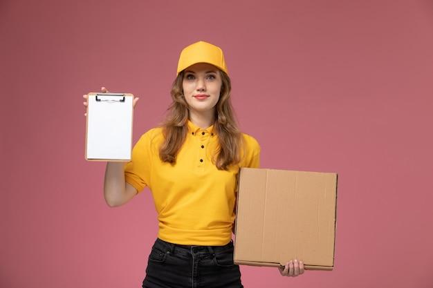 Junge weibliche kurierin der vorderansicht in der gelben uniform, die nahrungsmittelbox mit notizblock auf dem dunkelrosa hintergrunduniformlieferdienstjobarbeiter hält